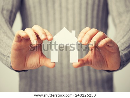 bright picture of man holding paper house - stock photo