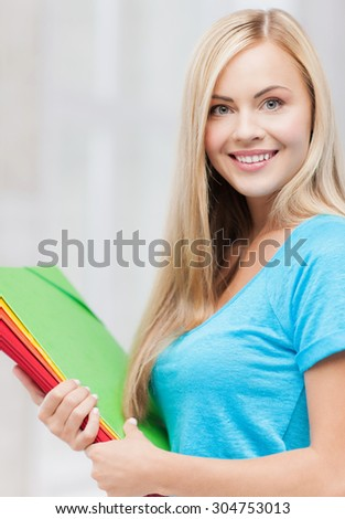 bright picture of smiling student with folders - stock photo