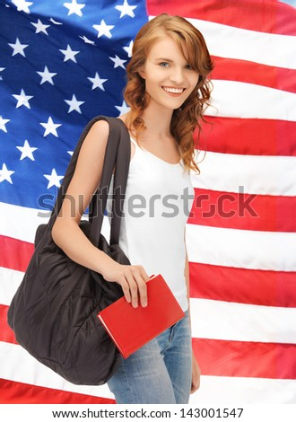 bright picture of travelling student with bag and book over american flag - stock photo