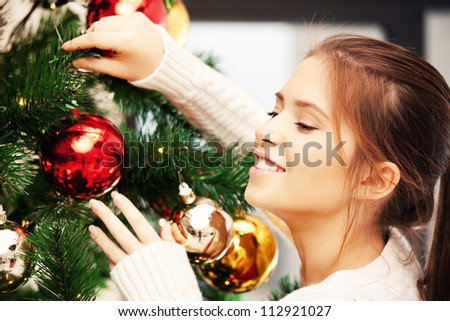 bright picture of woman decorating christmas tree - stock photo