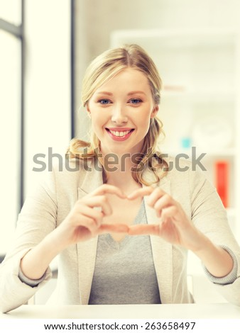 bright picture of young woman showing heart sign - stock photo