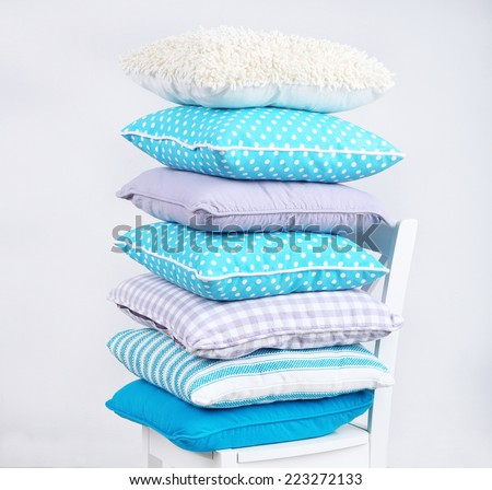 Bright pillows on chair in room - stock photo