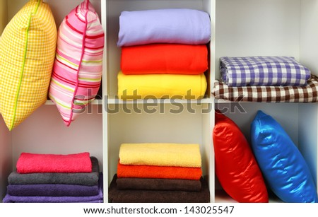 Bright pillows, towels and plaids on shelves, isolated on white - stock photo