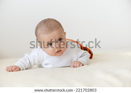 Bright portrait of a sweet little 5 months old baby boy looking up - stock photo