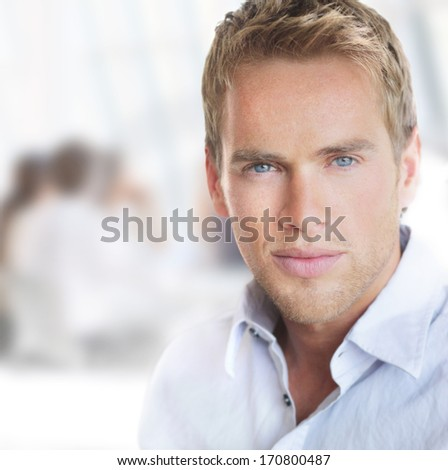 Bright portrait of a young good-looking successful businessman in office setting - stock photo