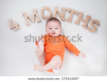 bright portrait of adorable baby. happy baby lying on white sheet and holding his legs - stock photo