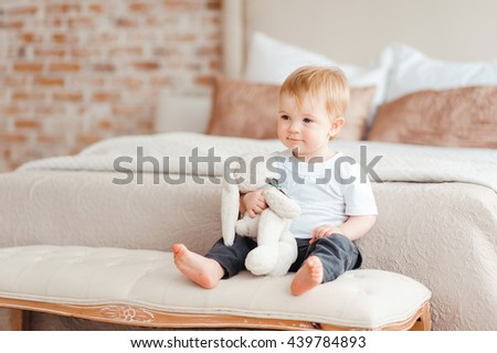 bright portrait of adorable baby with toy hare in her hands sitting on the banquette  - stock photo