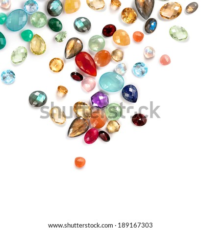 Bright precious and semiprecious gems on the white background. Many real stones: ruby, emerald, amethyst, garnet, citrine, blue topaz, peach and rainbow moonstone, prehnite, fluorite, carnellian ... - stock photo
