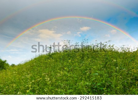 Bright rainbow in the sky with clouds above the hill - stock photo