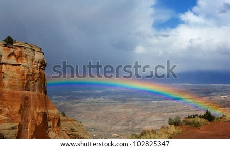 Bright rainbow over Grand Junction  Colorado from National Monument Park - stock photo