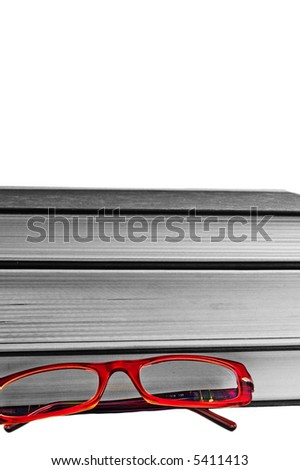 bright read glasses in-front of a stack of black and white books - stock photo