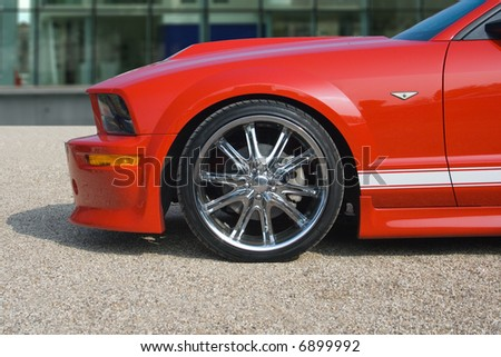 Bright red American muscle car with building in background - stock photo