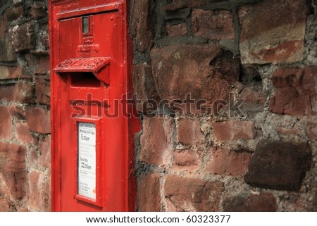 bright red postbox in old crumbling wall - closeup - stock photo