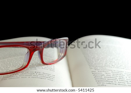 Bright red reading glasses on open book - stock photo