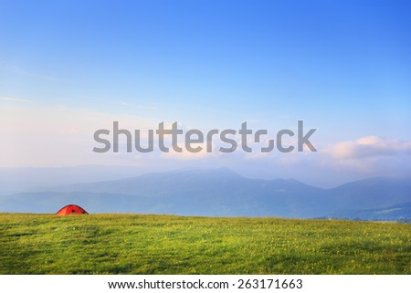 Bright red tent standing at mountain pasture on green grass with mountain landscape background under cloudy sky - stock photo