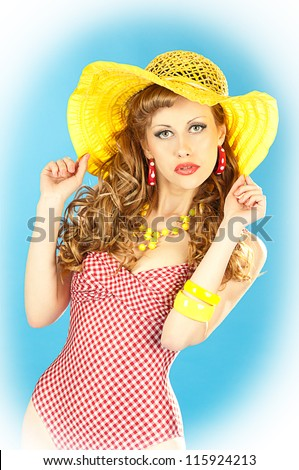 Bright seductive charming pin-up girl in a pink bathing suit and a broad yellow hat - stock photo