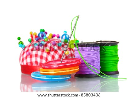 Bright sewing buttons, needle and skeins of thread isolated on white - stock photo