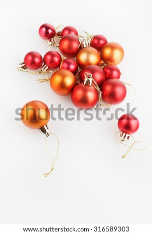 Bright shiny red and orange Christmas balls on a light background. Shallow depth of field. Selective focus. Space for text. Vertical shot. - stock photo