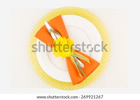 Bright simple spring table place setting with woven place mat, yellow charger, white plate, orange napkin, and silver utensils tied together with striped ribbon. - stock photo