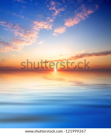 Bright sky and reflection in water during bright sundown. - stock photo