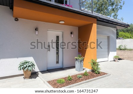 Bright space - a front door and a garage of a modern villa - stock photo
