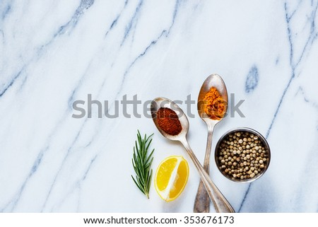 Bright spices in vintage metal spoons (curry and paprika) on marble table. Background layout with free text space. Cooking concept. Top view. - stock photo