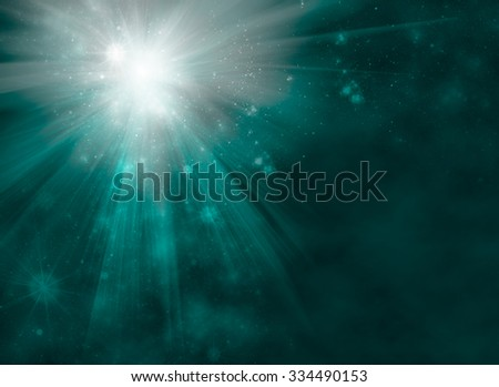 Bright starburst or fireworks with radiating rays of light on an abstract blue green blur background with flare sparkles and copy space for text - stock photo