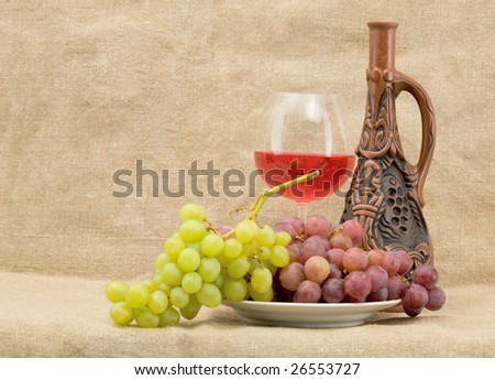 Bright still life with grapes and wine on sacking background - stock photo