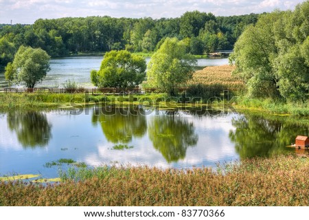 bright summer landscape with a lake and clouds - stock photo