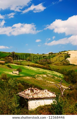 Bright summer landscape with little old stone house - stock photo