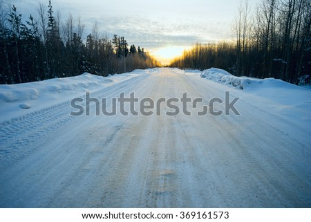 Bright sun at sunset in winter snow-covered road . - stock photo