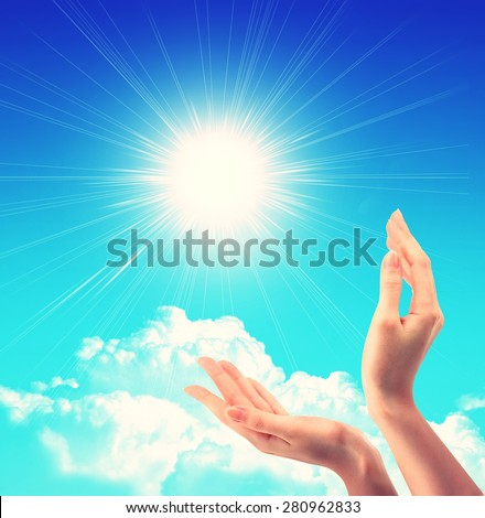 Bright sun between two hands over blue sky showing freedom or solar power concept - stock photo