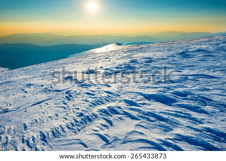 Bright sun in winter mountains covered with snow - stock photo