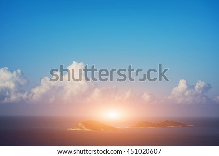 Bright sun rays in the blue sky over the sea and islands - stock photo