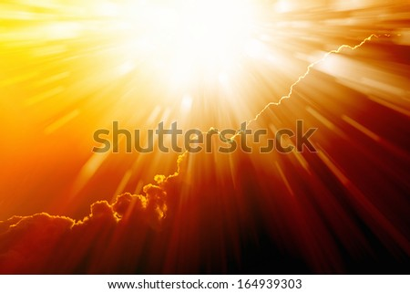 Bright sun shines from above, dark red clouds - stock photo