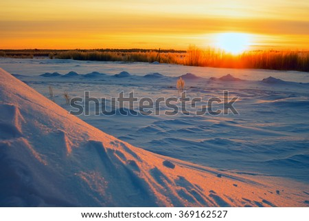 Bright sun  sunset in winter with large snow drifts. - stock photo