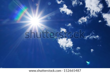 Bright sunburst with natural lens flare and radiating rays in a blue summer sky with fluffy white clouds and copyspace - stock photo