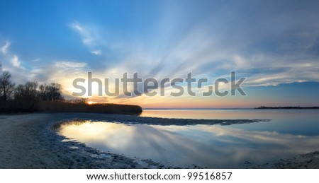 Bright sundown and reflections in water. Panoramic composition - stock photo