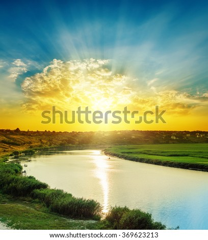 bright sunset in clouds over river - stock photo