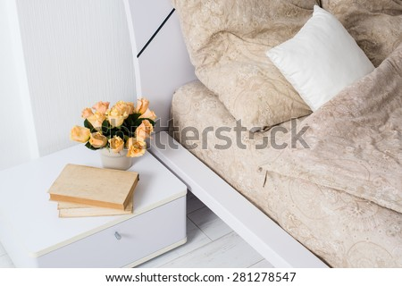 Bright white bedroom interior, cozy bed with beige linen, flowers on a bedside table, closeup - stock photo