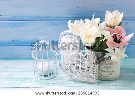 Bright white daffodils and tulips  flowers, candle on turquoise  painted wooden planks against blue wall. Selective focus is on flowers. Place for text.  - stock photo