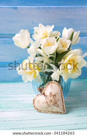 Bright white daffodils and tulips  flowers in blue vase and decorative heart  on turquoise  painted wooden planks against blue wall. Selective focus. Love and St. Valentines Day concept. - stock photo