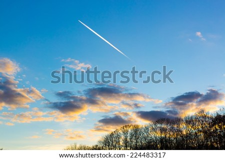Bright white trail aircraft in the cloudy sky at sunset - stock photo