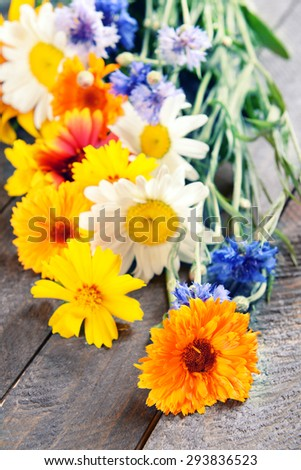 Bright wildflowers on wooden table, closeup - stock photo