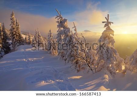 Bright winter landscape with beautiful sunshine. Sunset in the mountain valley. Carpathians, Ukraine, Europe - stock photo