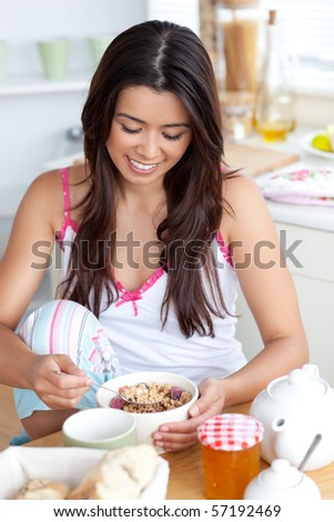 Bright woman eating muesli with fruits sitting in the kitchen - stock photo