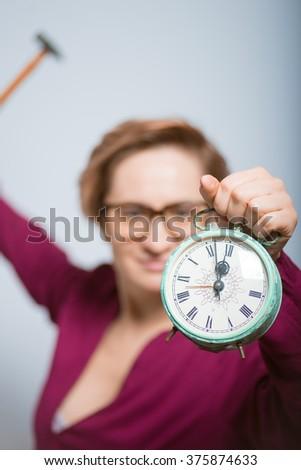 bright woman wants to break the clock, isolated studio - stock photo