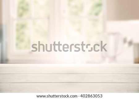 Bright wooden table against empty kitchen with vegetables - stock photo