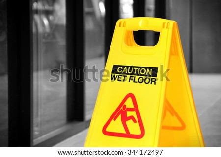Bright yellow caution sign of wet floor in a hallway. Conceptual image with isolated color over black and white background - stock photo
