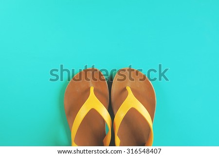 Bright yellow flip flops on mint green background with copy-space. Summer colors style. Minimalism. Concept of vacation, travel, summer, shopping. - stock photo